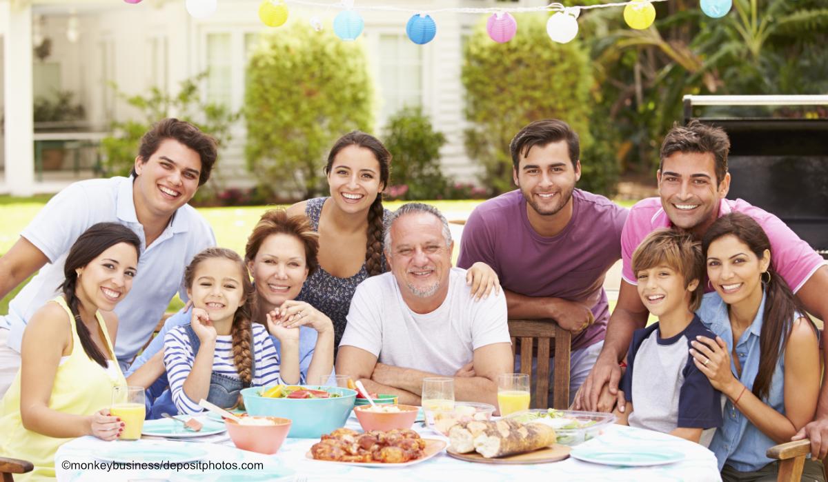 Großfamilie beim Essen an einer festlichen Tafel im Garten